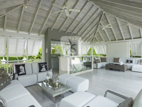 Lounge in the covered pool side living area with bar and ample seating whilst overlooking the pool