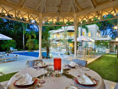 The enchanting dining gazebo set for dinner with pool, garden and villa views