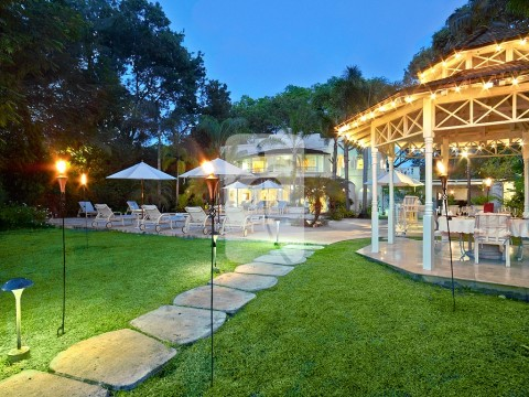 A enticing night shot of the villa and its charming dining gazebo to the right