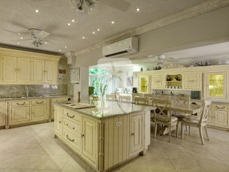 The gourmet kitchen has custom cabinetry by Joshua Jones of the UK, wide marble countertops and more
